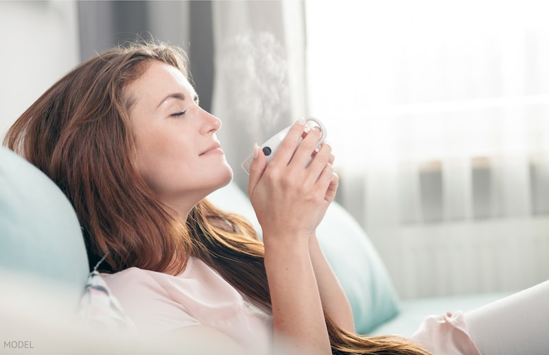 Young woman sitting on couch at home and drinking coffee, casual style indoor shoot